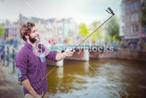 Composite image of happy hipster using selfie stick