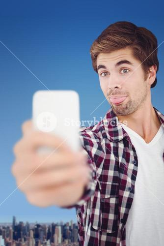 Composite image of hipster making face while taking selfie