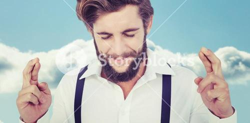 Composite image of hipster with fingers crossed