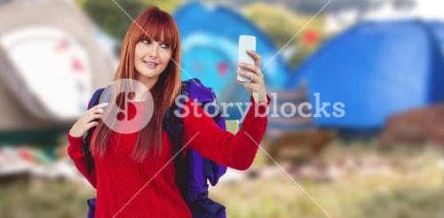 Composite image of smiling hipster woman with a travel bag taking selfie