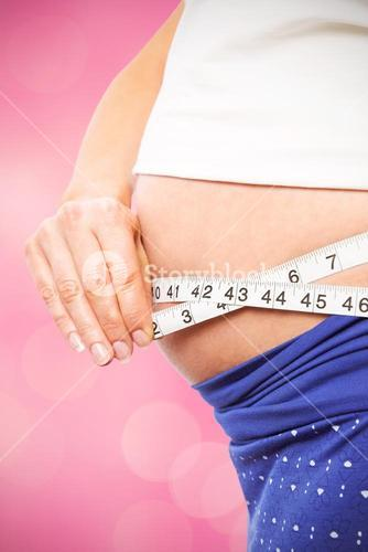 Composite image of pregnant woman measuring her bump