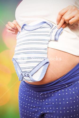 Composite image of pregnant woman holding baby clothes