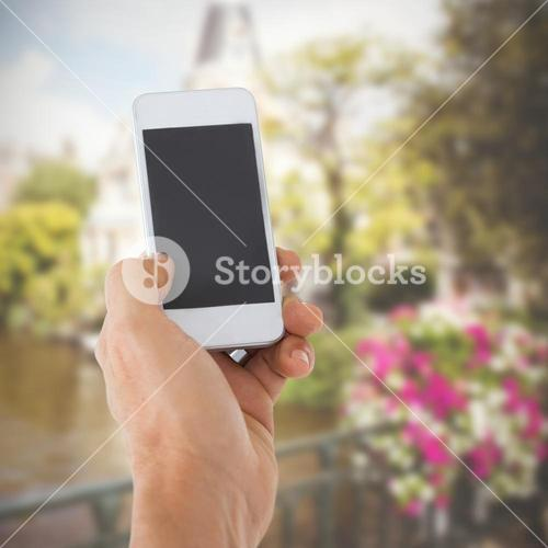 Composite image of male hand holding a smartphone