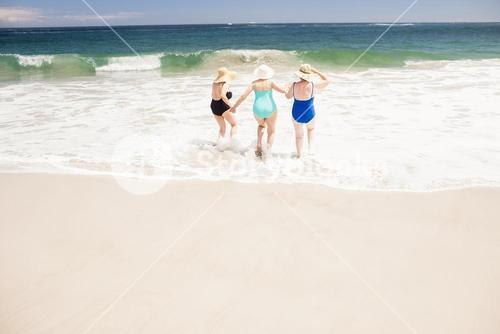 Senior woman friends running into water