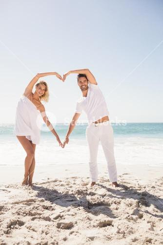Smiling young couple doing heart shape