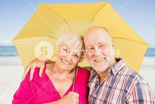 Smiling senior couple holding umbrella