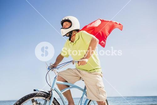 Senior superhero riding bike