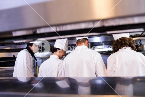 Group of chefs in white uniform busy to preparing food