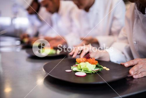 Close-up of chef decorating food plate