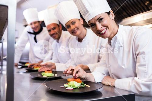 Smiling chef while decorating food plate