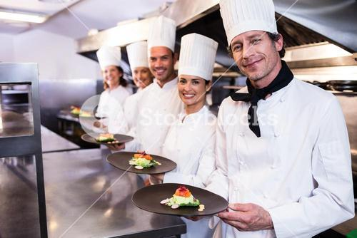 Happy chefs presenting their food plates