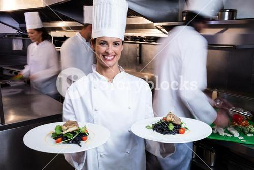 Happy chef presenting her food plates