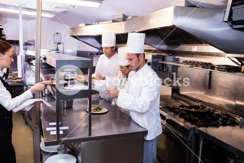 Group of chef preparing food in commercial kitchen