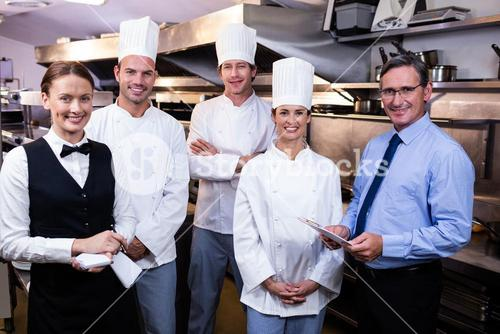 Happy restaurant team standing together in commercial kitchen