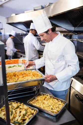 Chef standing at serving trays of pasta