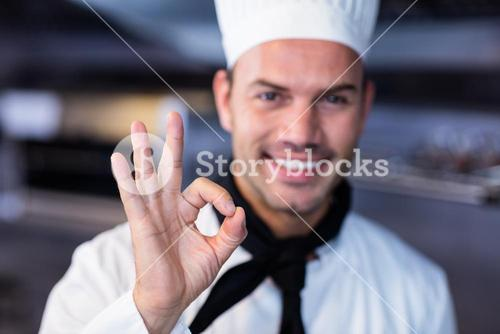 Happy chef making ok sign in commercial kitchen