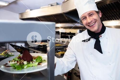 Portrait of a chef handing dinner plate through order station