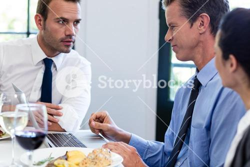 Businessmen discussing during a business lunch meeting