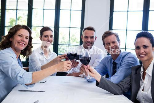 Portrait of businesspeople toasting wine glass during business lunch meeting