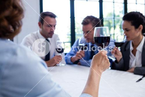 Group of businesspeople drinking wine glass during business lunch meeting