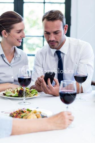 Business colleagues looking at mobile phone during business lunch meeting
