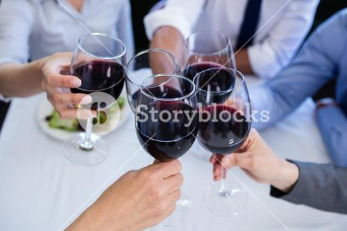 Hands toasting wine glasses