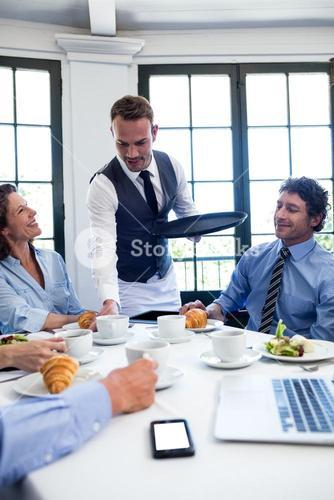 Waiter serving coffee to business people