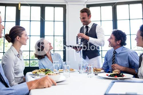 Waiter serving water to business people
