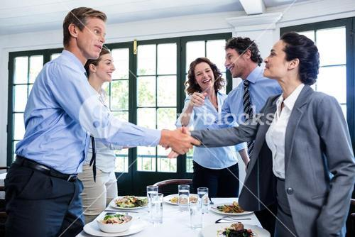 Business colleagues shaking hands after a successful lunch meeting