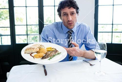Frustrated man holding a plate of meal in restaurant