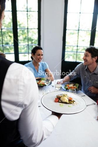 Waiter serving meal to customers