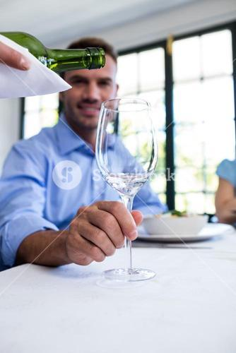 Waiter pouring wine in a glass of costumer