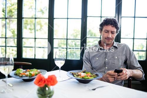 Man in a restaurant using mobile phone
