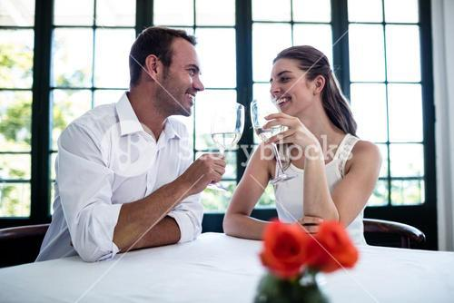 Couple toasting wine glasses at dining table
