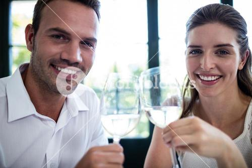 Portrait of couple toasting wine glasses at dining table