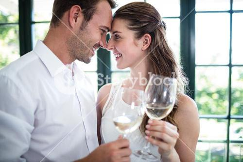 Couple toasting wine glasses in a restaurant
