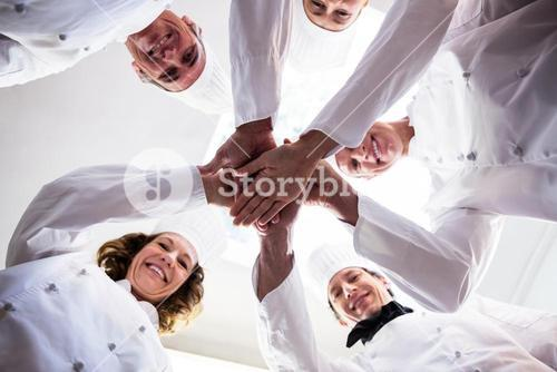 Portrait of chefs team putting hands together and cheering