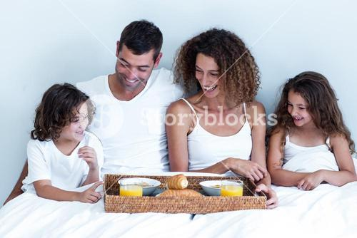 Happy family sitting with breakfast tray on bed