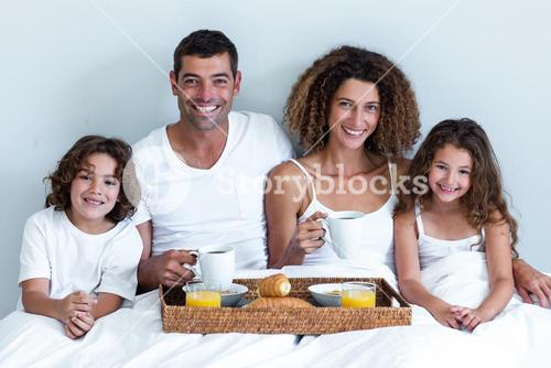 Portrait of a family sitting with breakfast tray in bed
