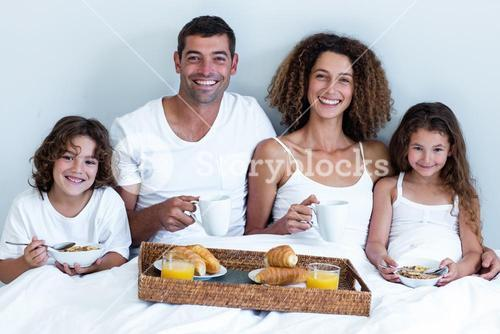 Portrait of family having breakfast in bed