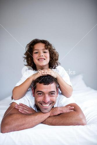 Portrait of a son lying on fathers back
