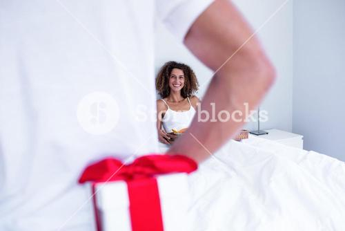 Man hiding gift behind his back for wife