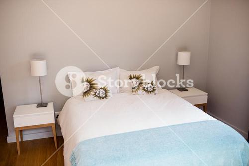 Empty bed with white bed sheet