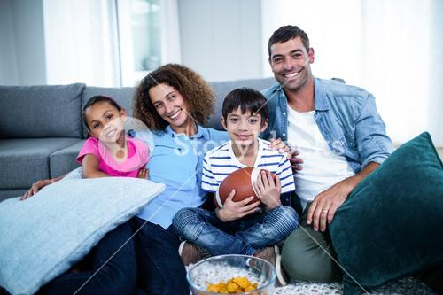 Portrait of family watching american football match on television