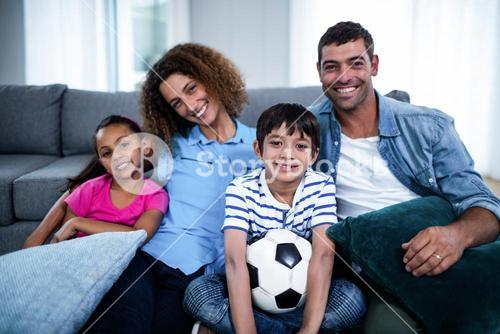 Portrait of family watching match together on television