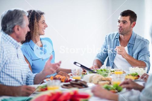 Happy family talking while having breakfast