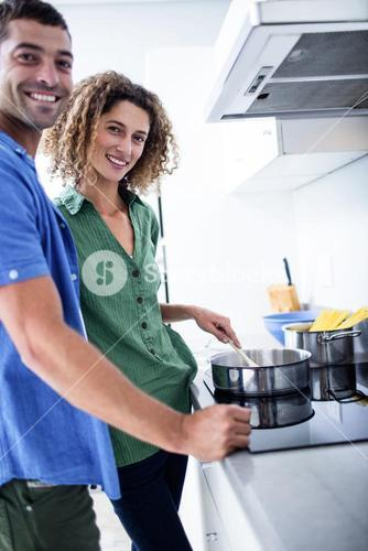 Portrait of couple cooking in kitchen