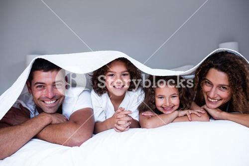 Portrait of happy family lying under a bedsheet