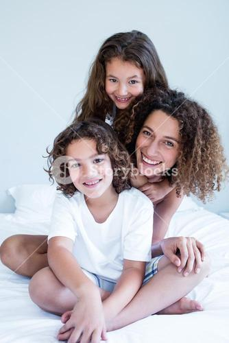 Portrait of mother and children sitting together on bed