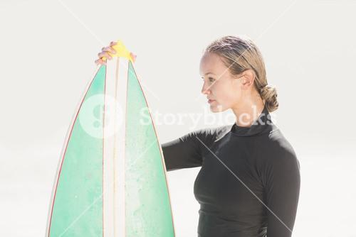 Woman in wetsuit holding a surfboard